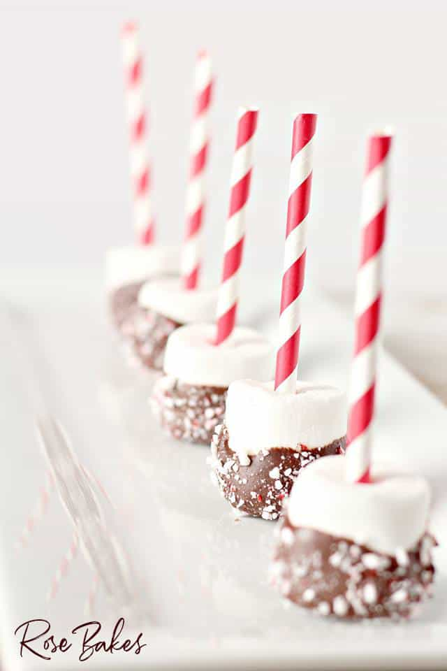 Peppermint Dipped Marshmallows for Hot Cocoa on red and white straws lined up on platter