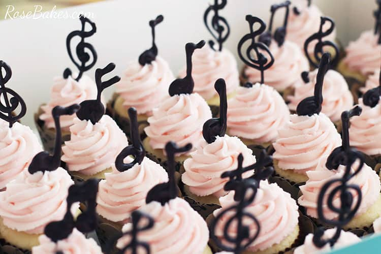 Cupcakes with light pink frosting and chocolate music note toppers.