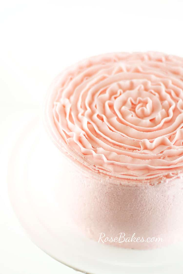 Cake frosted in light pink buttercream that is smooth on the sides and has a ruffly textured top.