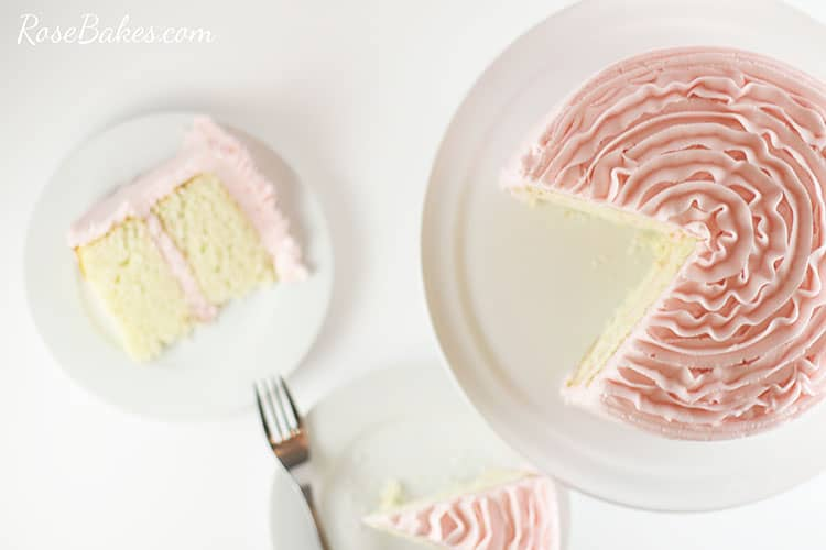 Overhead view of the light pink ruffle cake with a couple of slices taken out.  The slices of cake are beside the cake stand on white plates.