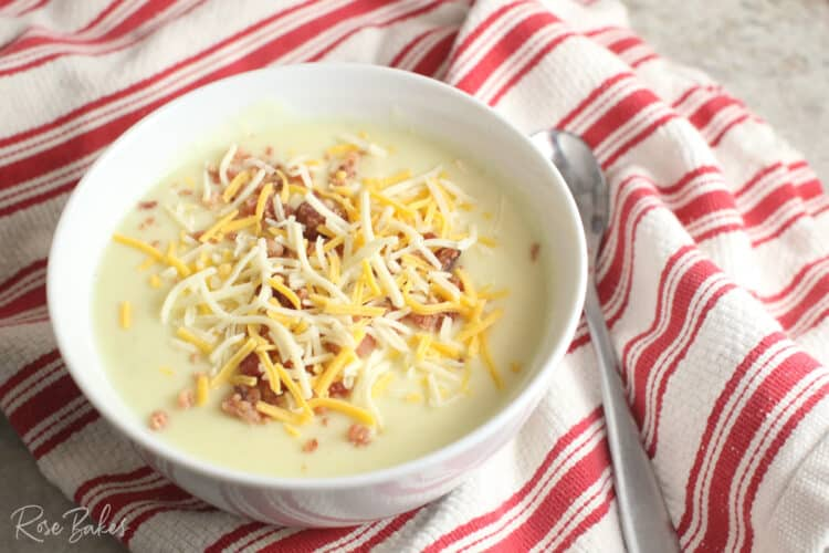 White bowl filled with cream cheese potato soup topped with shredded cheese and crumbled bacon.  The bowl is sitting on top of a red and white striped towel with a silver spoon next to it.