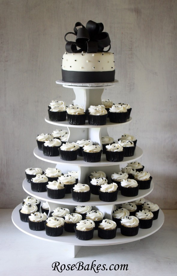 the cake and cupcakes are displayed on a smart baker stand which i