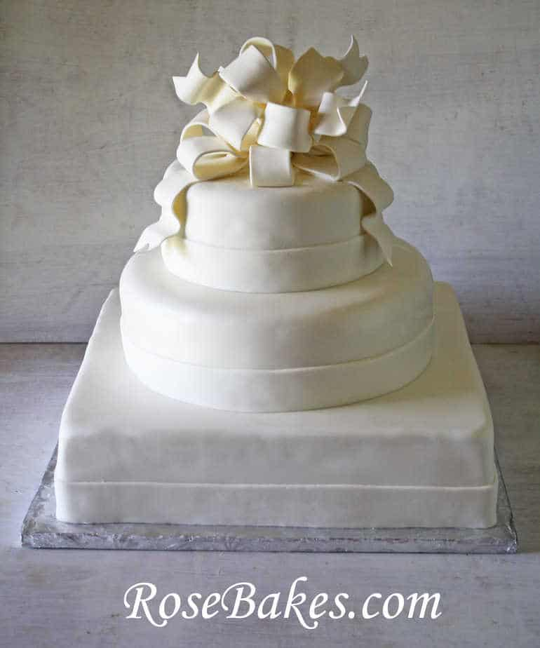 elegant all white wedding cakes white wedding cake with poofy gum paste bow 13954