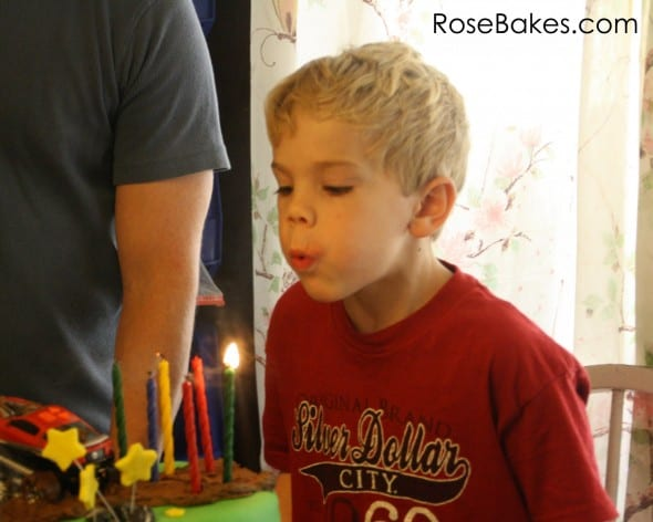 Christian Blowing Out Candles on Mud Riding Cake