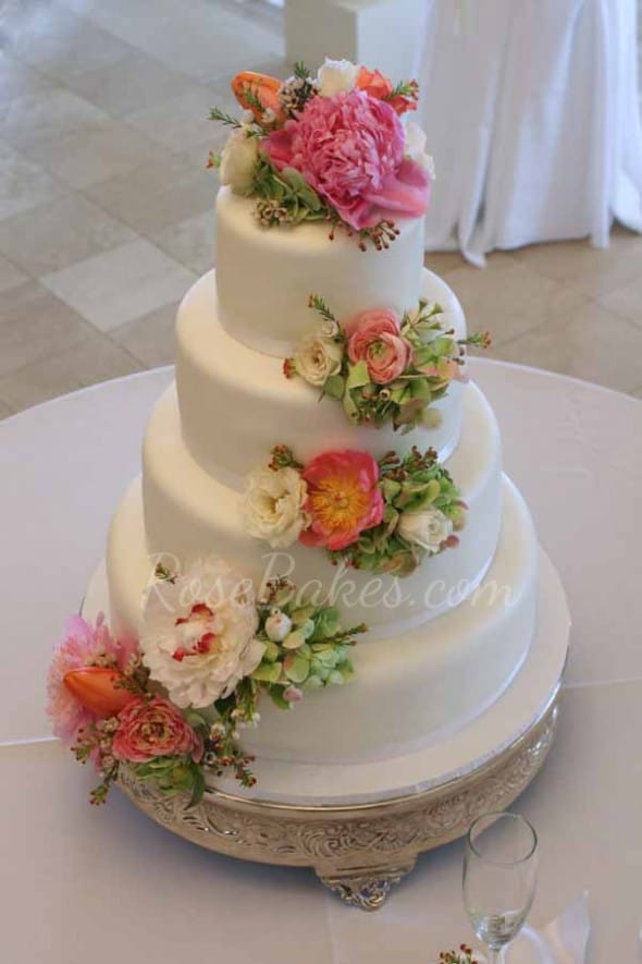 Cascading Fresh Flowers On White Wedding Cake With Ribbons