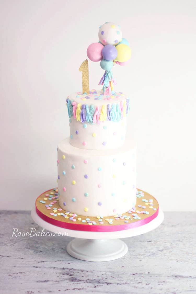using melted candy melts for how to stick fondant decorations to cake on balloons and tassels cake