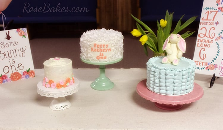 Three Somebunny is One cakes on cake stands.