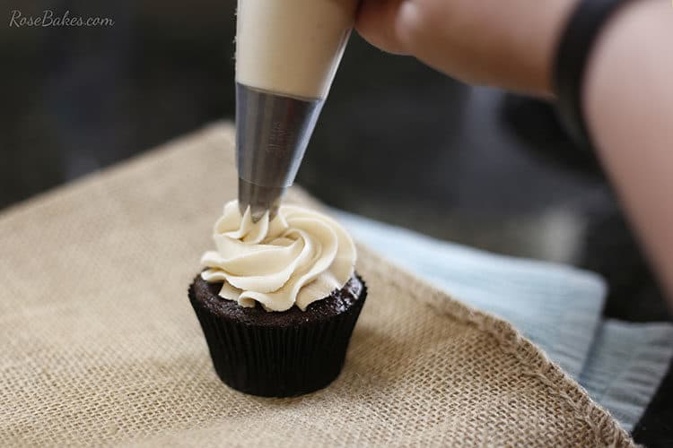 Chocolate cupcake with maple brown sugar buttercream being piped onto it.