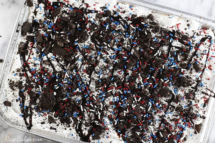 Top view of the pan of ice cream sandwich cake with Oreo crumbs and red white and blue sprinkles