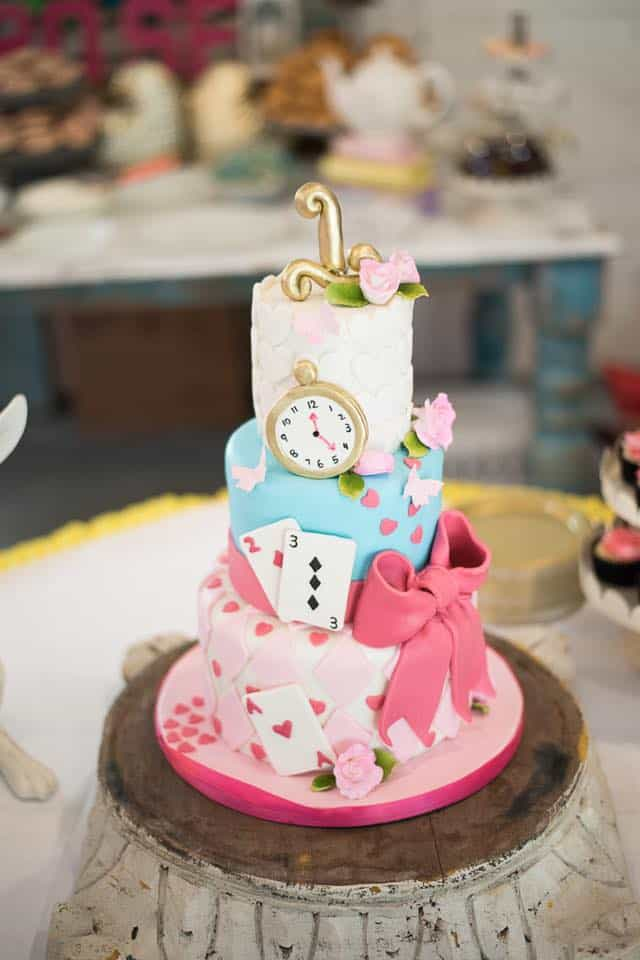 3 tier alice in wonderland birthday cake with pink bow and clock