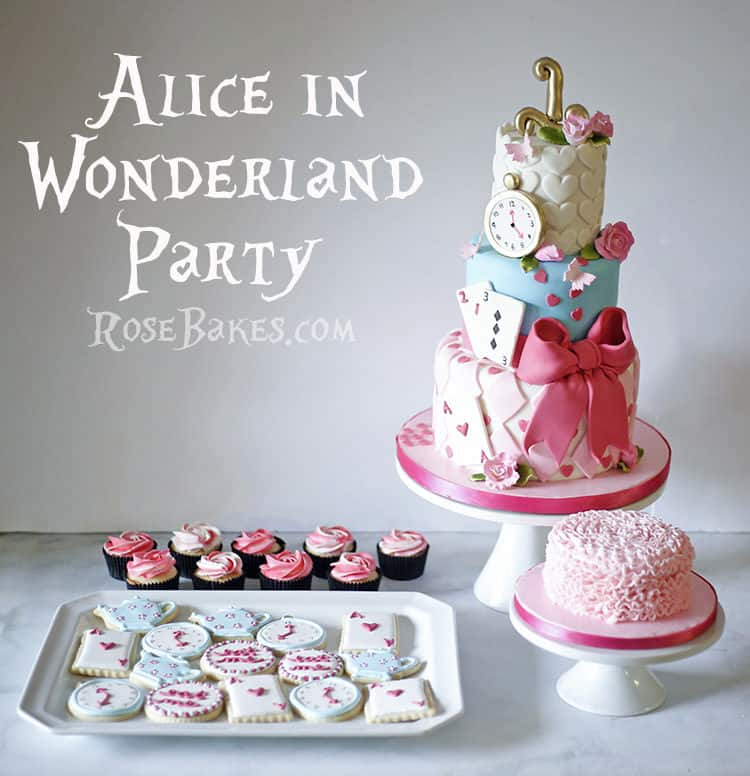 Party display of alice in wonderland cake and pink cupcakes and white cookies