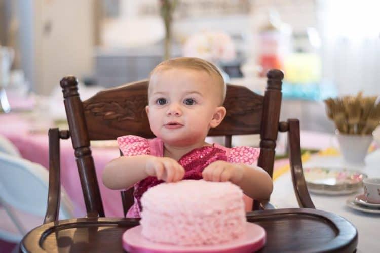 baby girl in high chair grabbing pink smash cake