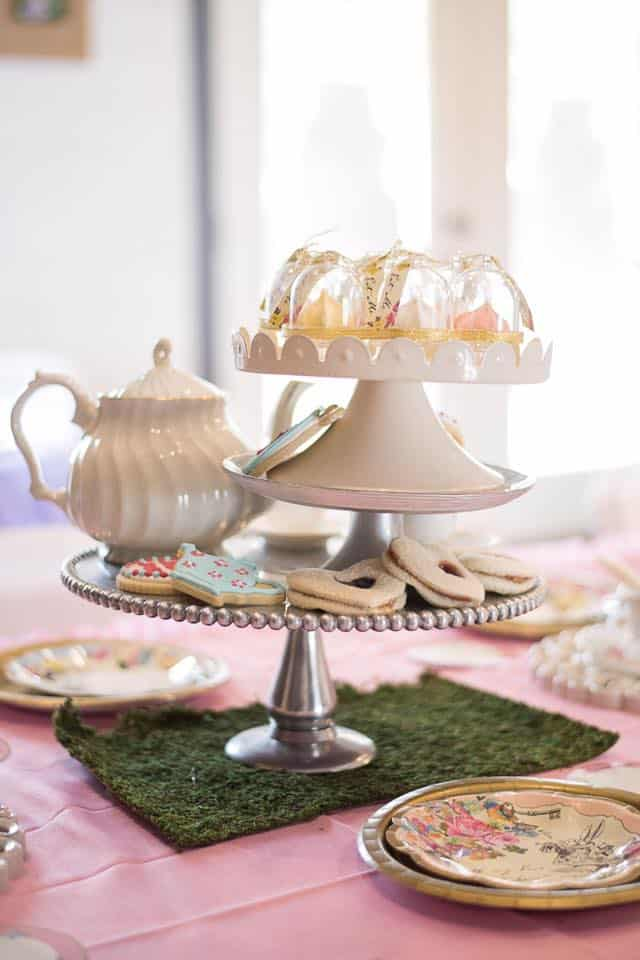 silver cake stand displaying pretty pink tea pot and cookies