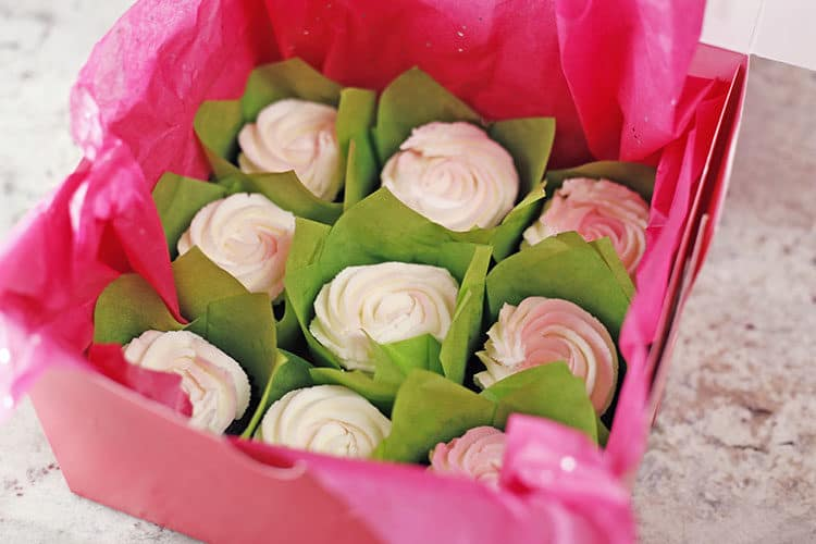 buttercream roses cupcakes in box with green tulip liners and tissue paper for cupcake bouquets
