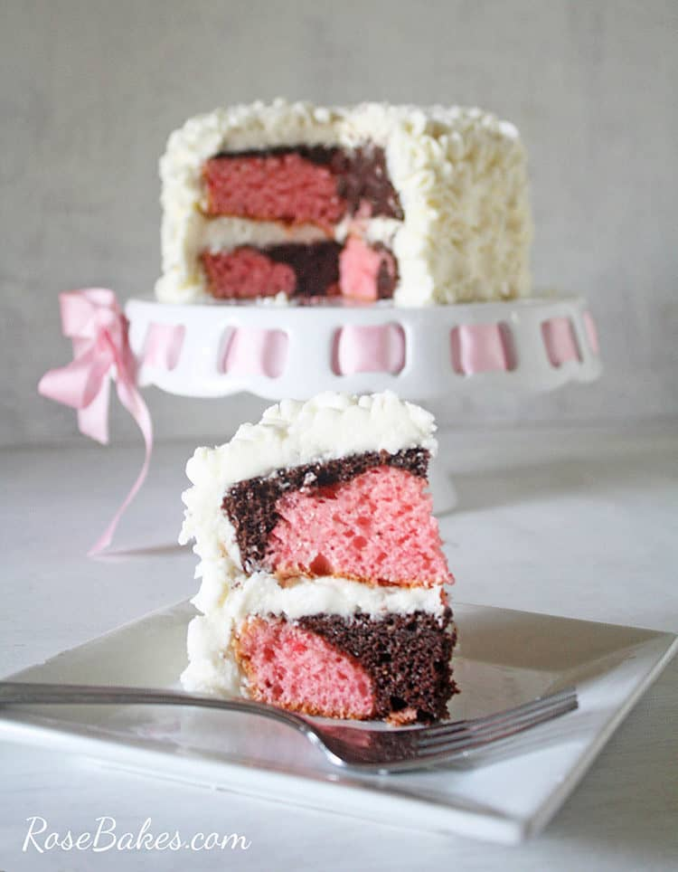 slice of messy ruffles cake - chocolate and strawberry swirled cake on plate with fork