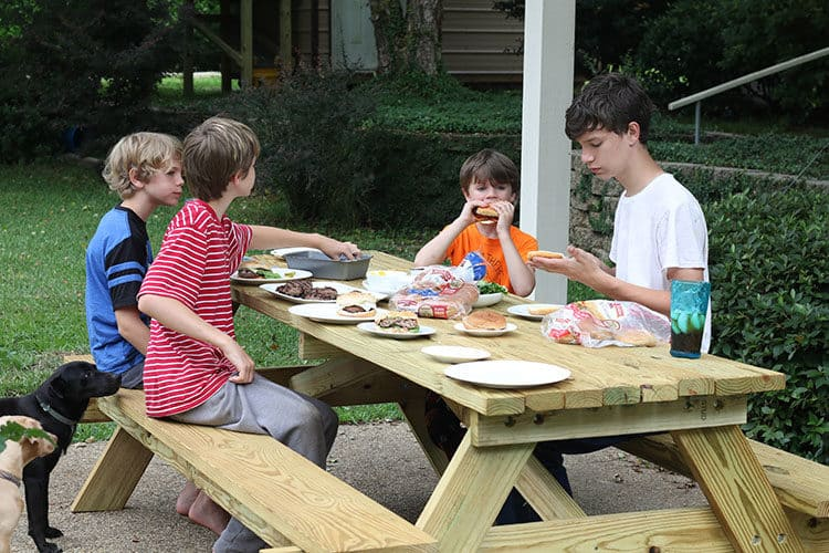 Kids at picnic table in back yard eating burgers