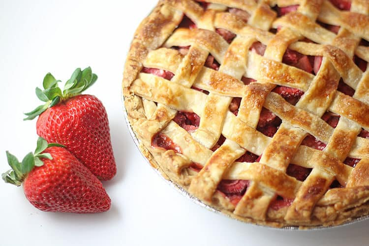 Strawberry Rhubarb Pie whole with fresh strawberries