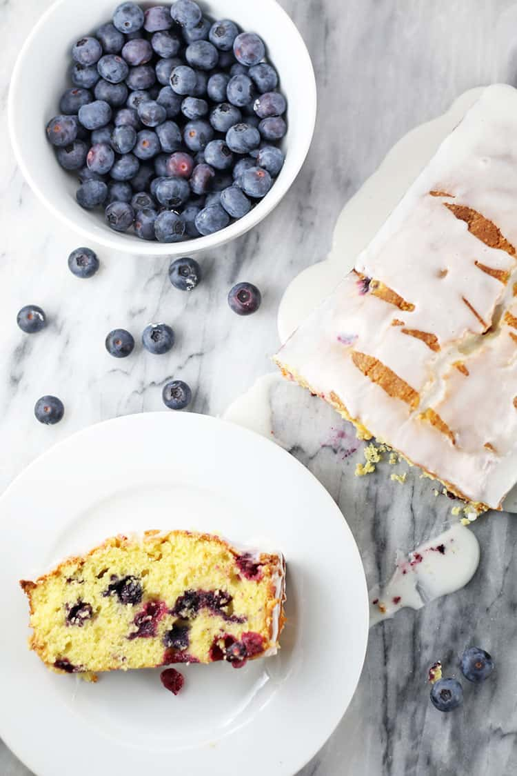 Lemon Blueberry Loaf Cake with a slice on a cake and a bowl of fresh blueberries