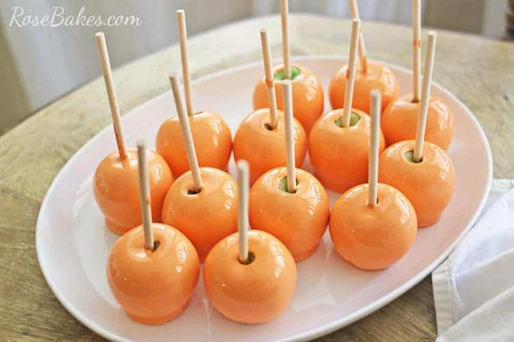 orange candy apples on white platter for how to prevent bubbles on candy apples