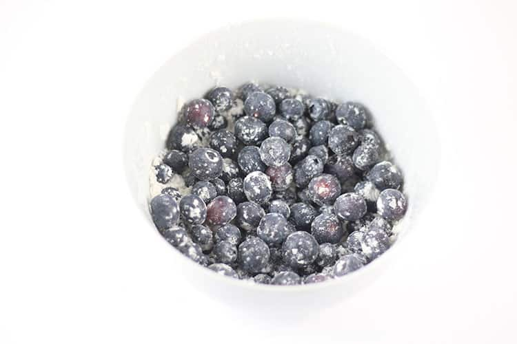 Blueberries tossed with flour in a white bowl