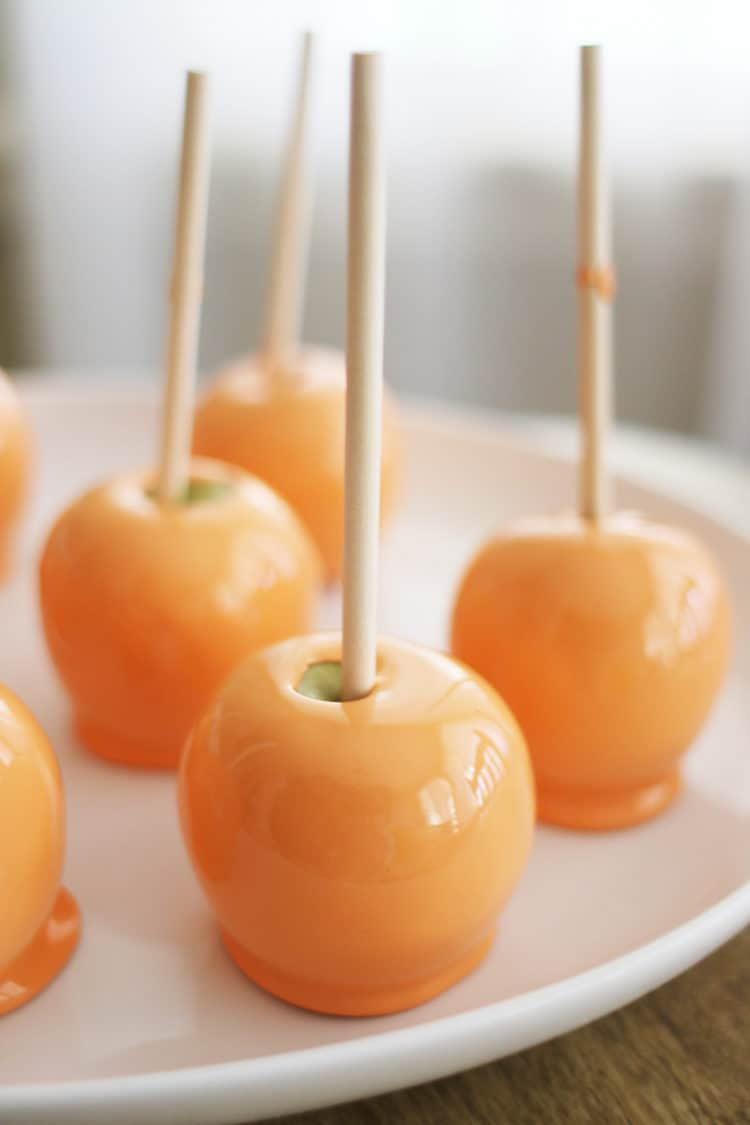 orange candy apples on white platter for how to prevent bubbles on candy apples post