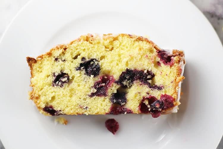 slice of lemon blueberry loaf cake on white plate