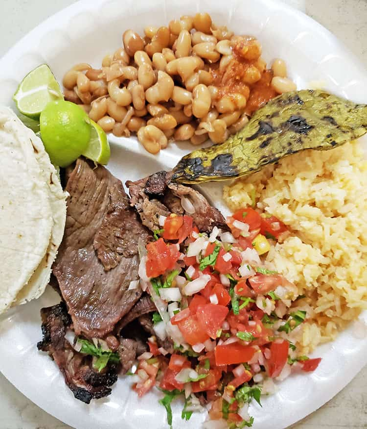 Carne Asada with spanish rice, fresh warm tortillas, pico de galla, fresh limes and beans