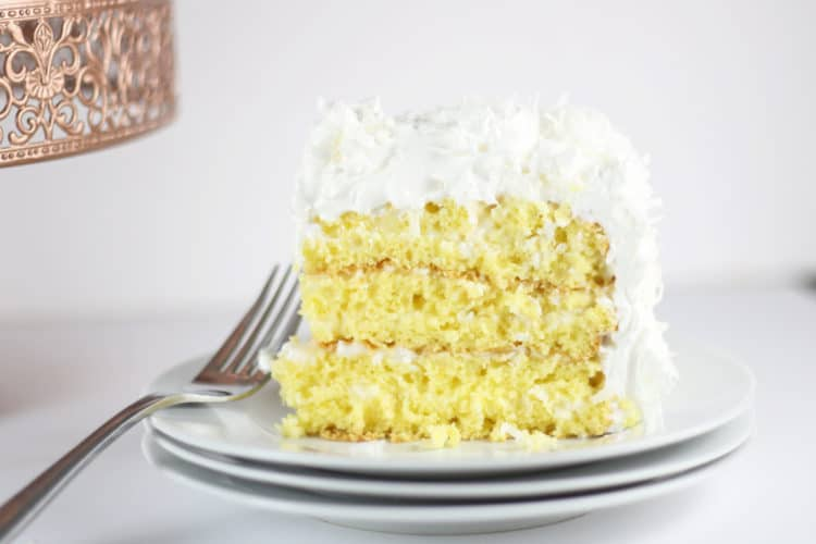 slice of coconut cake on white plate with fork