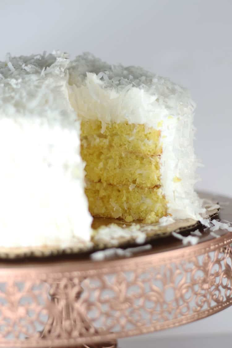 coconut cake with slice missing on rose gold cake stand