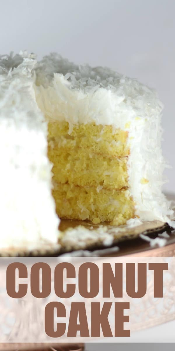 sliced coconut cake with missing piece on rose gold cake stand