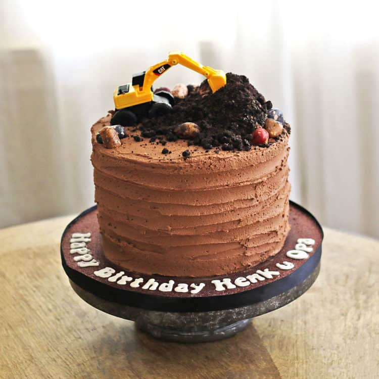 A chocolate cake with OREO dirt on top and a toy excavator.