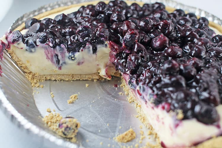 lemon blueberry no bake cheesecake with a few slices missing