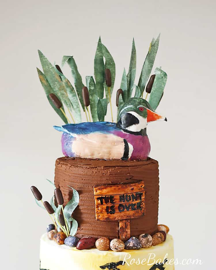 mallard duck cake topper with wafer paper grass and reeds behind it on duck hunting groom's cake