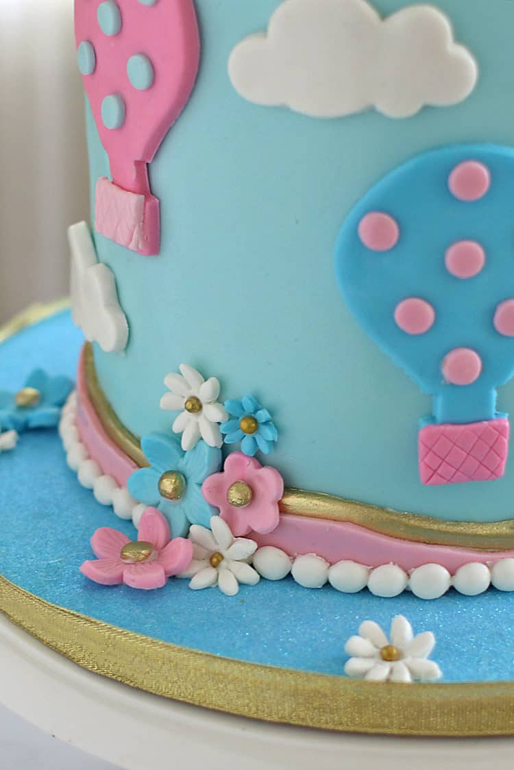 Blue bottom tier hot air balloons cake with flowers and border