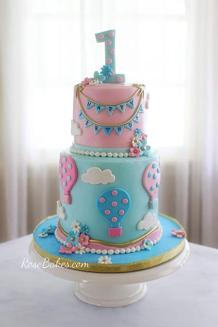 Pink and blue hot air balloon cake with bunting and flowers