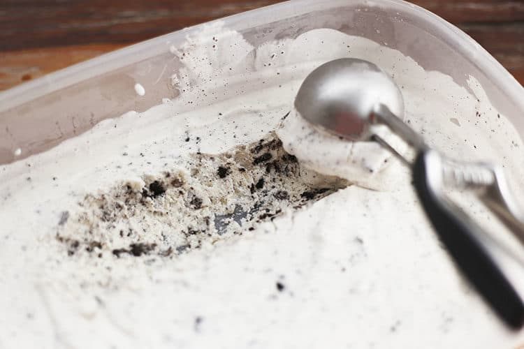 Homemade OREO Cookies and Cream Ice Cream being scooped from plastic freezer bowl
