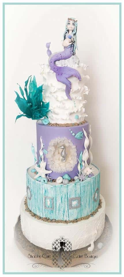Mermaid Baby Shower Cake with sculpted mermaid topper ruffles and seaweed