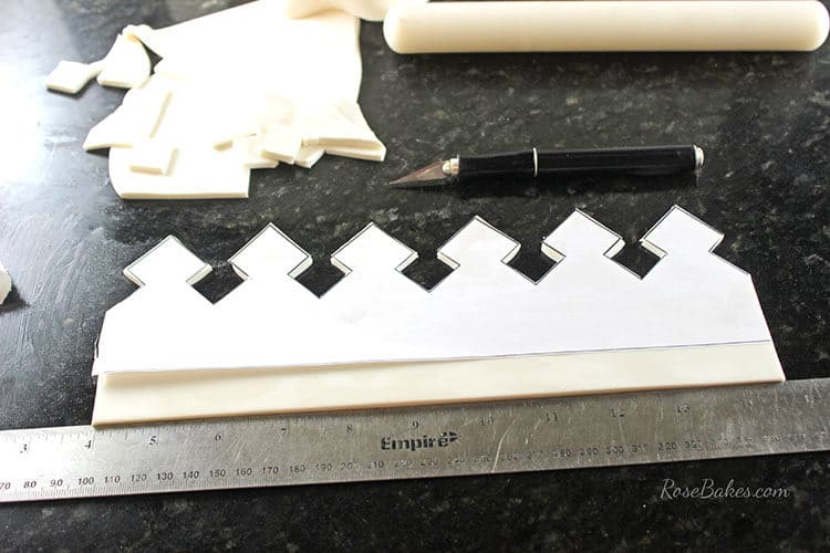 cutting out crown cake topper template on gum paste