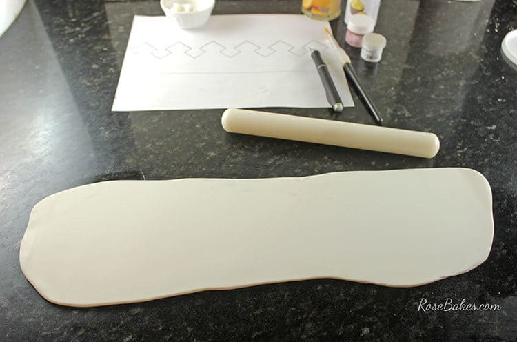 Rolling out gum paste for crown cake topper