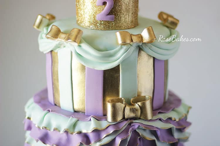 top tier of princess cake with stripes and gold bows and draping fondant