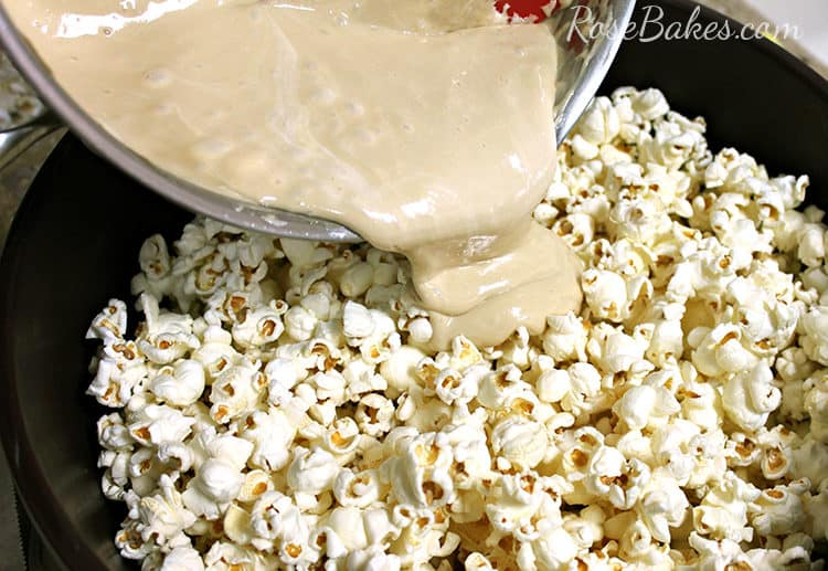 Making Marshmallow Caramel Popcorn Balls by pouring caramel sauce over popcorn