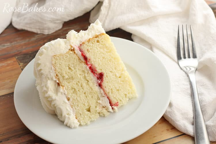 white cake with raspberry filling and vanilla buttercream on a white plate