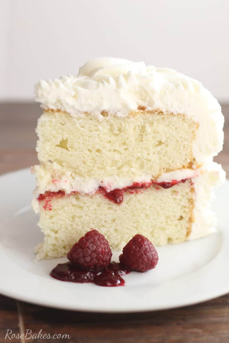 white cake with vanilla buttercream and raspberry filling on a white plate with fresh raspberries