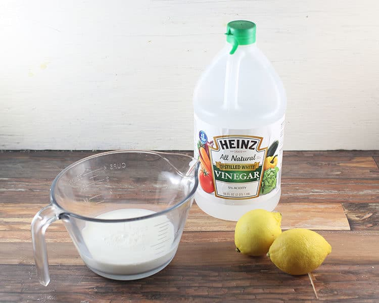cup of milk with lemons and white vinegar bottle