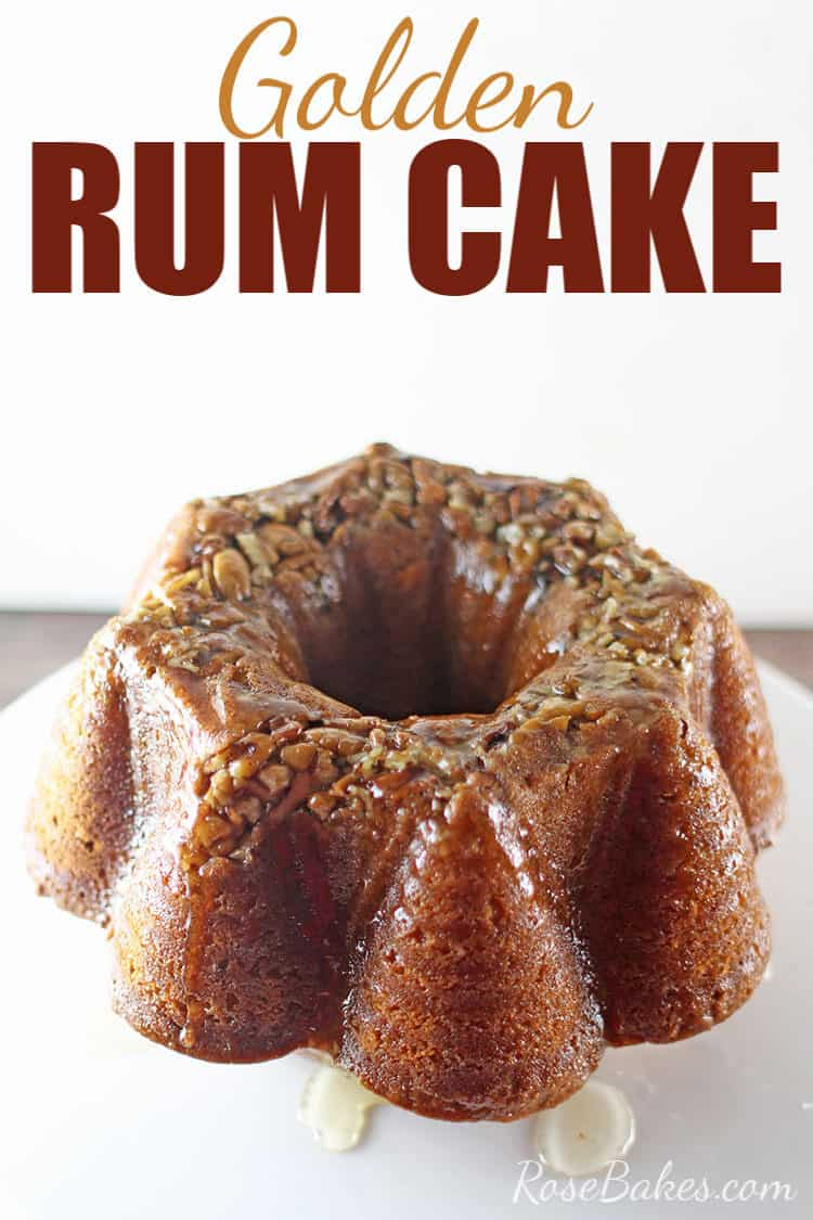 Golden Rum Cake with pecans and rum sauce on on a white cake stand