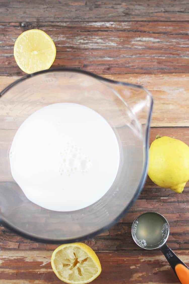 how to make buttermilk - cup of milk with sliced lemons and measuring spoon