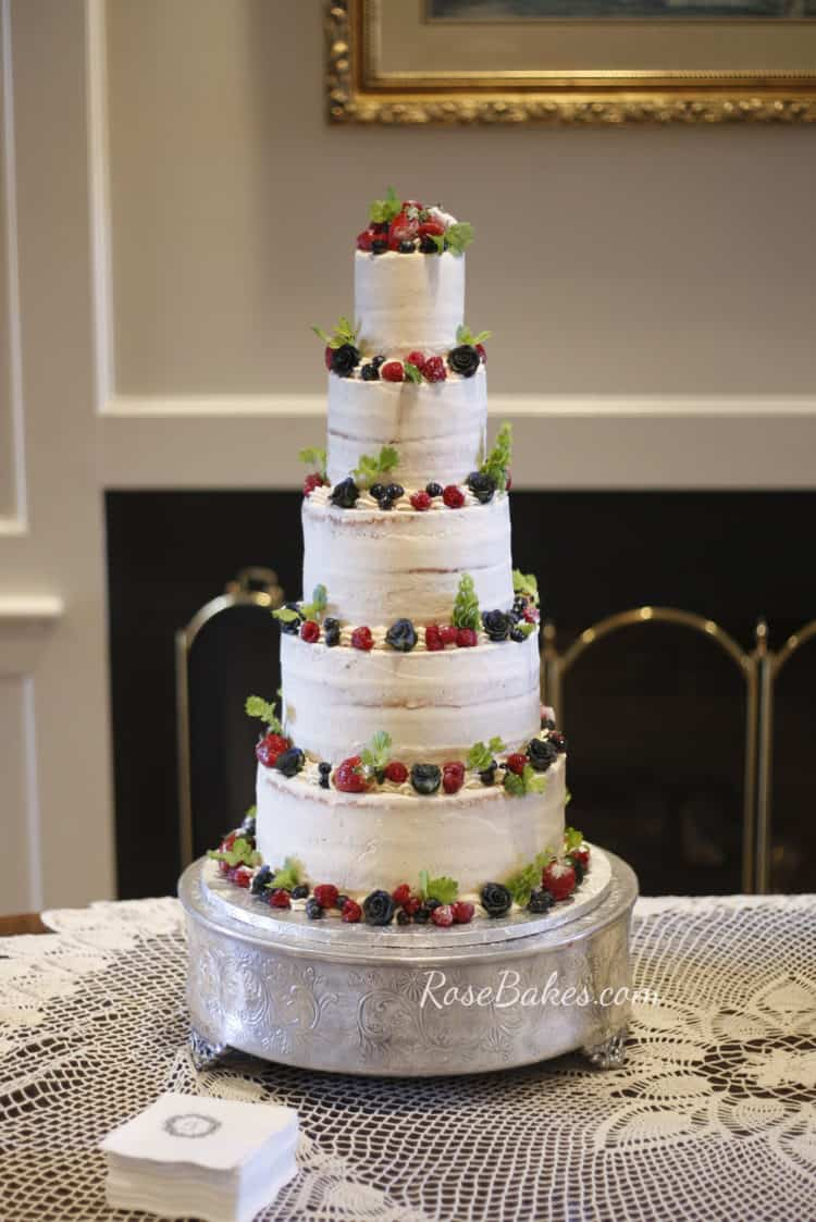 Semi Naked Wedding Cake with Fresh Fruit and Greenery on Silver Stand