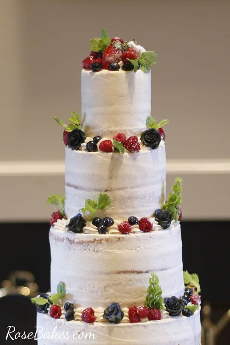 Close up of Semi Naked Wedding Cake with Fresh Fruit and Greenery