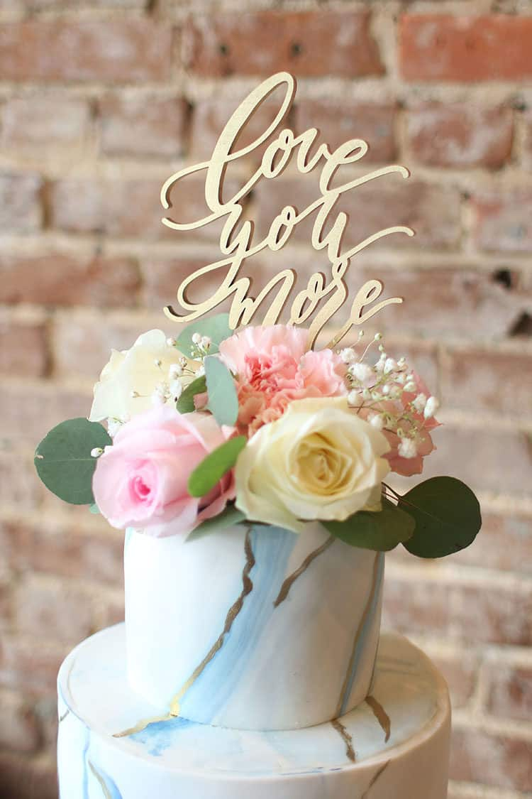"Marbled Fondant Wedding Cake with Navy, Gold and Pink with ""Love You More"" cake topper and flowers"