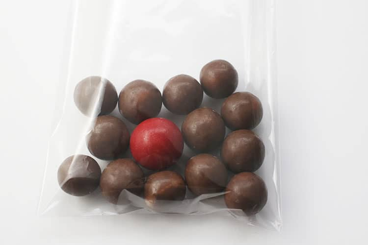 whoppers and red candy in treat bag for Reindeer Noses Treat Bags